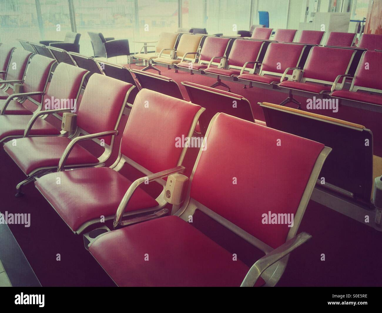 Empty chairs in waiting area at departure lounge within Terminal 1 of Charles de Gaulle international airport in Stock Photo
