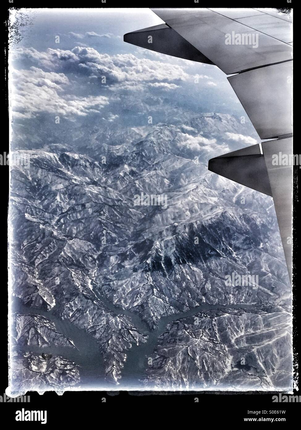 Aerial view of airplane wing, mountains, rivers and clouds as seen from window of airplane. Black vintage frame.Stock Photo