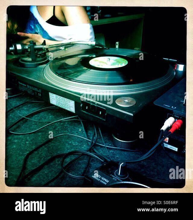 Dj decks spinning vinyl record old school background - Stock Image