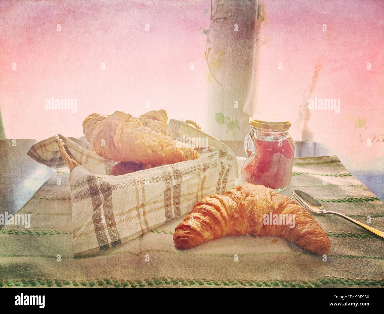 Small jar of homemade strawberry jam, bread basket with croissant, striped cloth and silver spoon. Vintage texture Stock Photo
