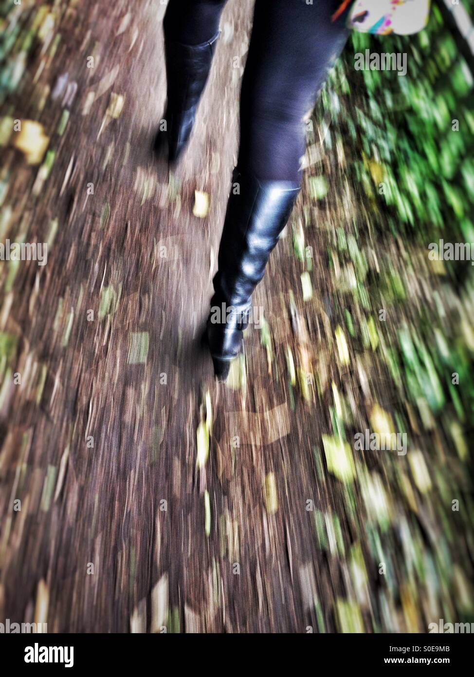 Motion blur of adult female legs wearing boots quickly walks away along a rural pathway - Stock Image