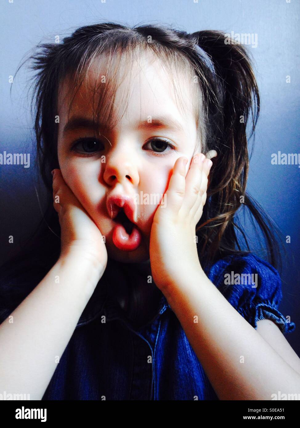 3-year old girl making funny face - Stock Image