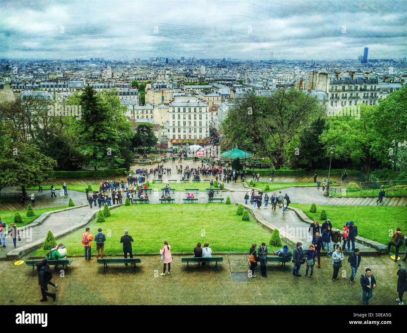 City day views of Paris in Spring as seen from Montmarte hill in France. Tourists in foreground, Montparnasse Tower Stock Photo