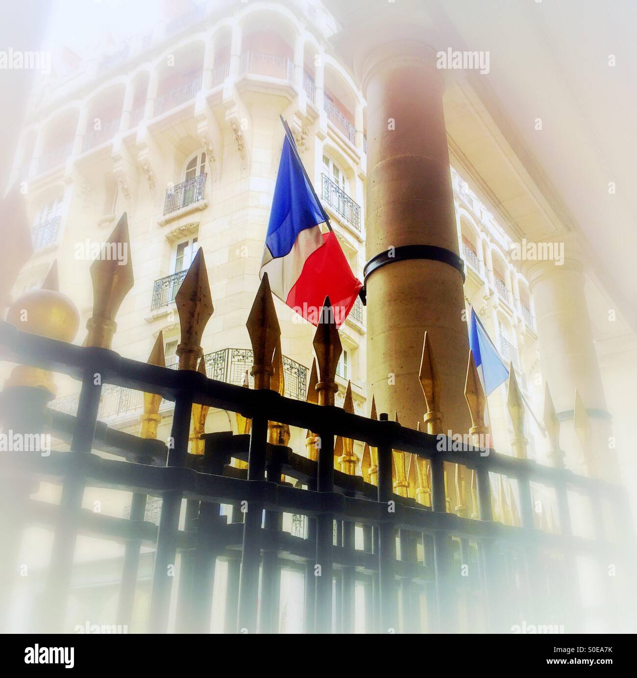 French flag on classic column with gold and black gate in foreground and beautiful traditional Parisian apartmentStock Photo