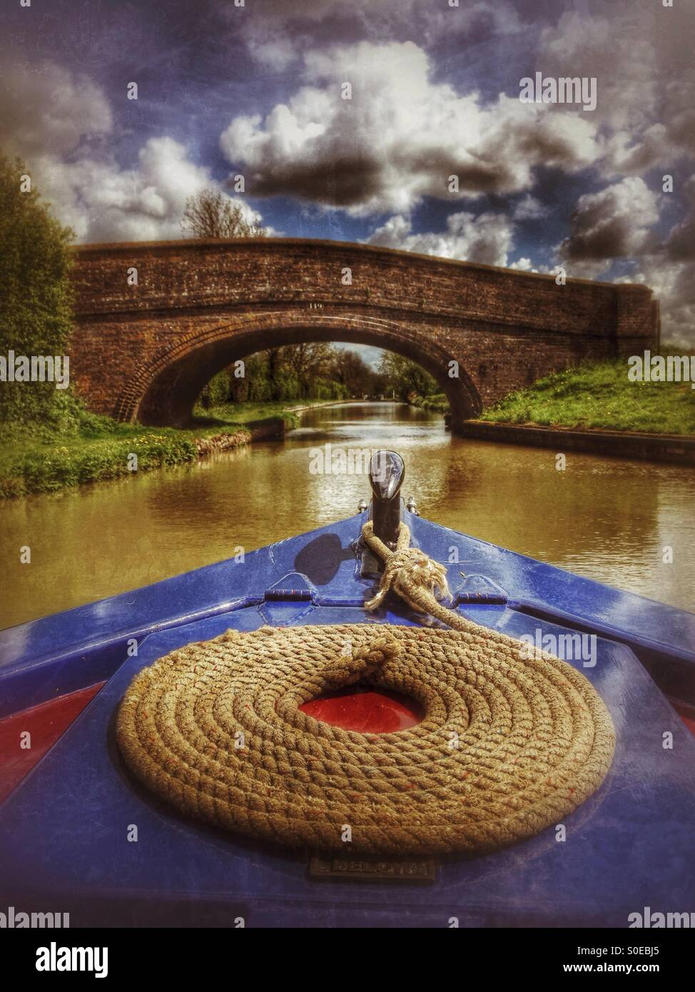 Narrowboat approaching a bridge over the South Oxford Canal near Cropredy, Oxfordshire, England. - Stock Image