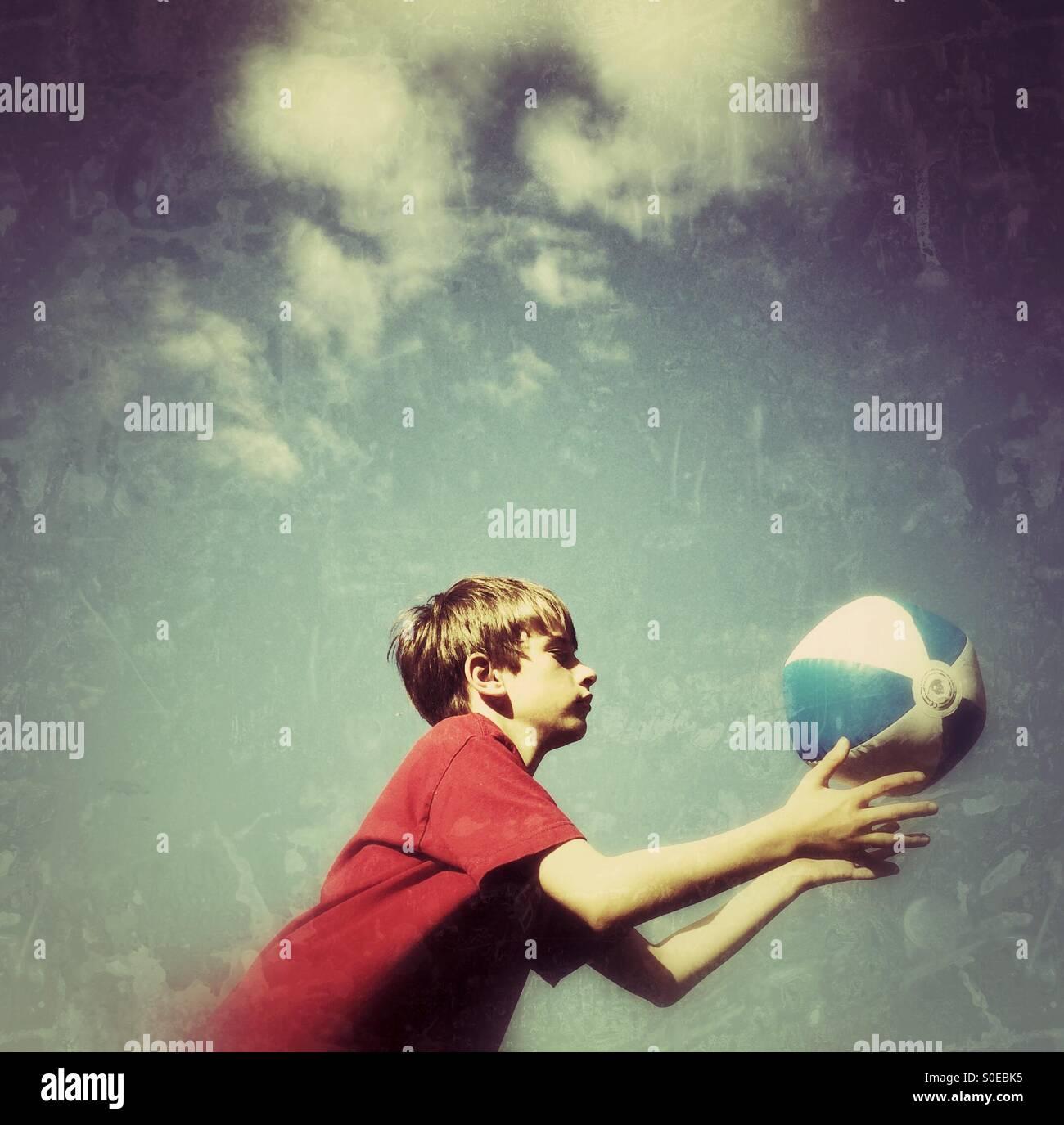 A boy catching a beach ball - Stock Image