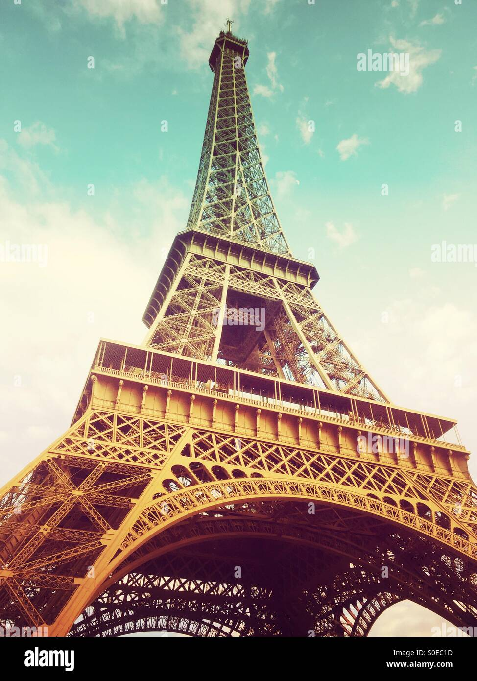 View of Eiffel Tower from below, along Champs de Mars in Paris, France. Warm, retro tones. Stock Photo