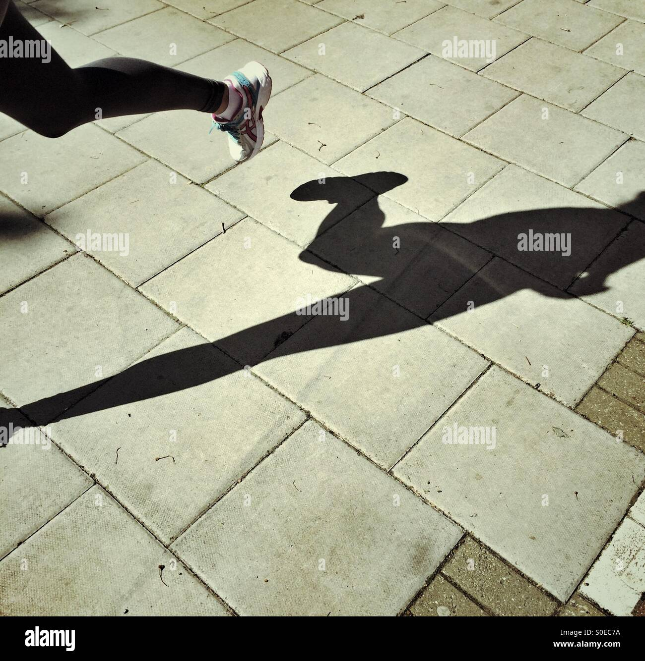 Shadow of an athlete who is running - Stock Image