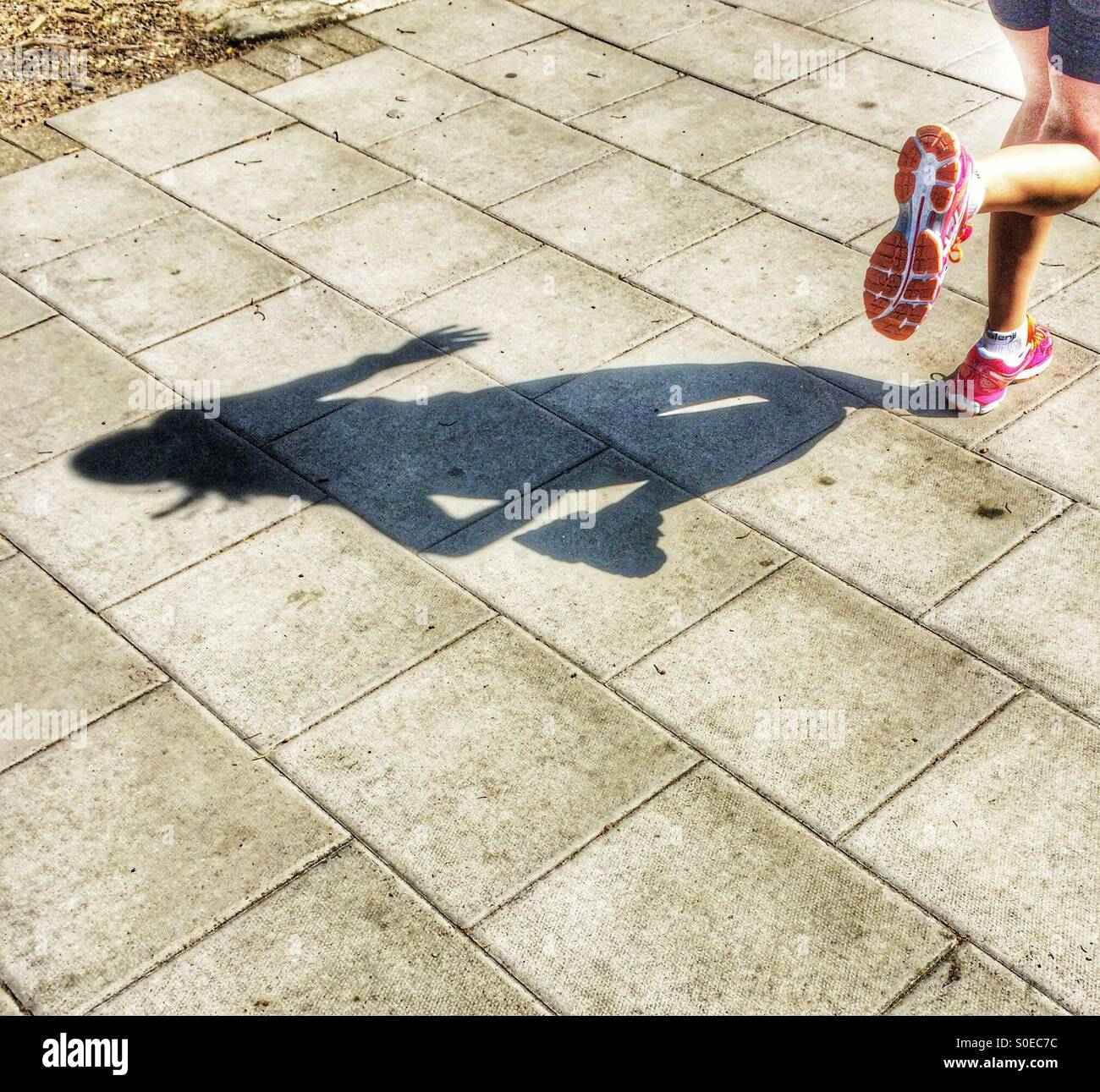 A shadow of an athlete running on the street. - Stock Image