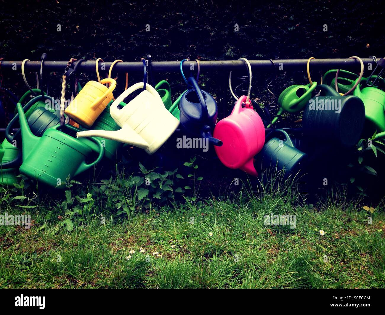 Plastic Watering cans attached to a metal bar on a cemetery in Berlin Kreuzberg - Stock Image