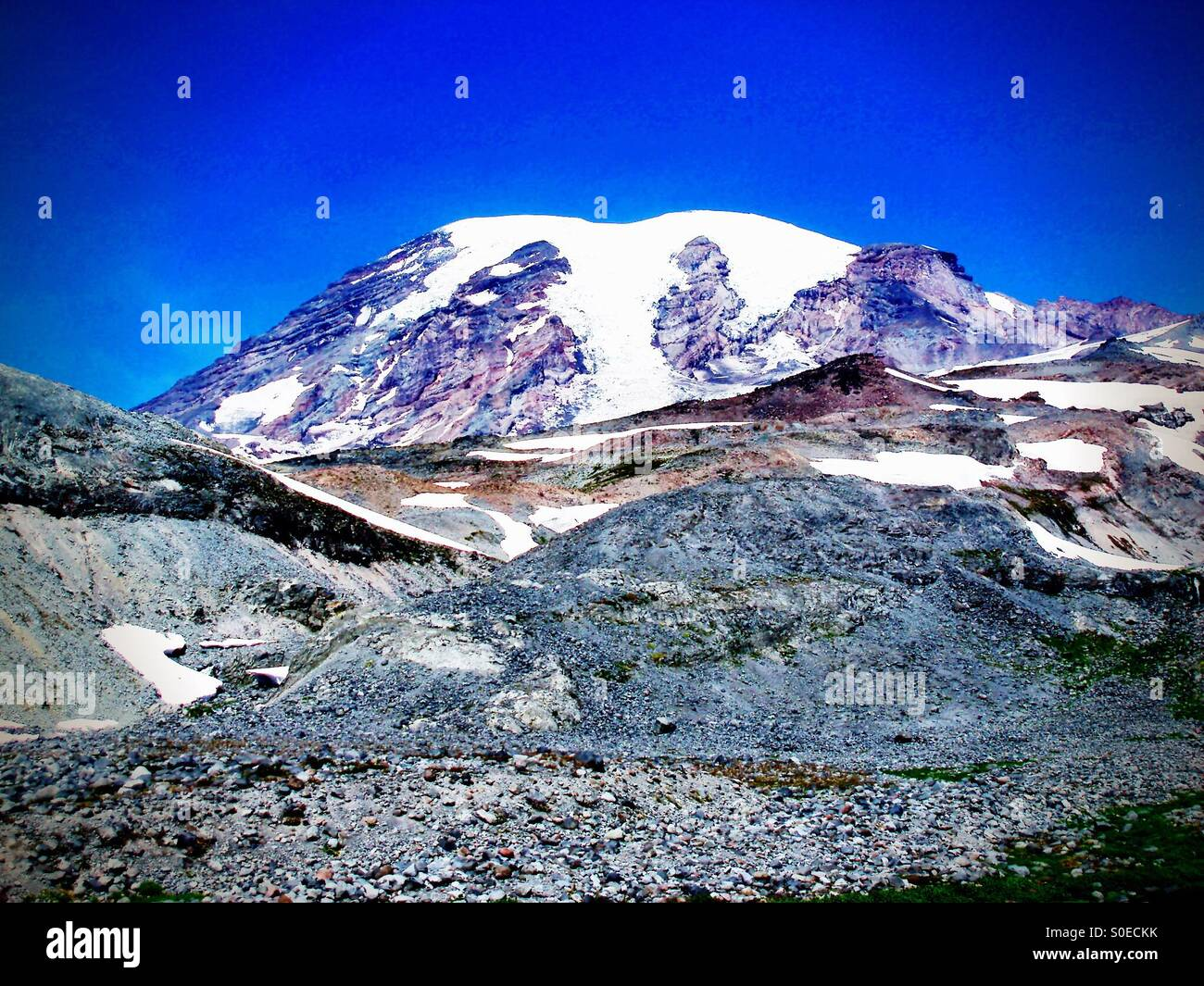 Summit ancient glacier, lava rock, mountain climbing under perfect clear blue skies - Stock Image