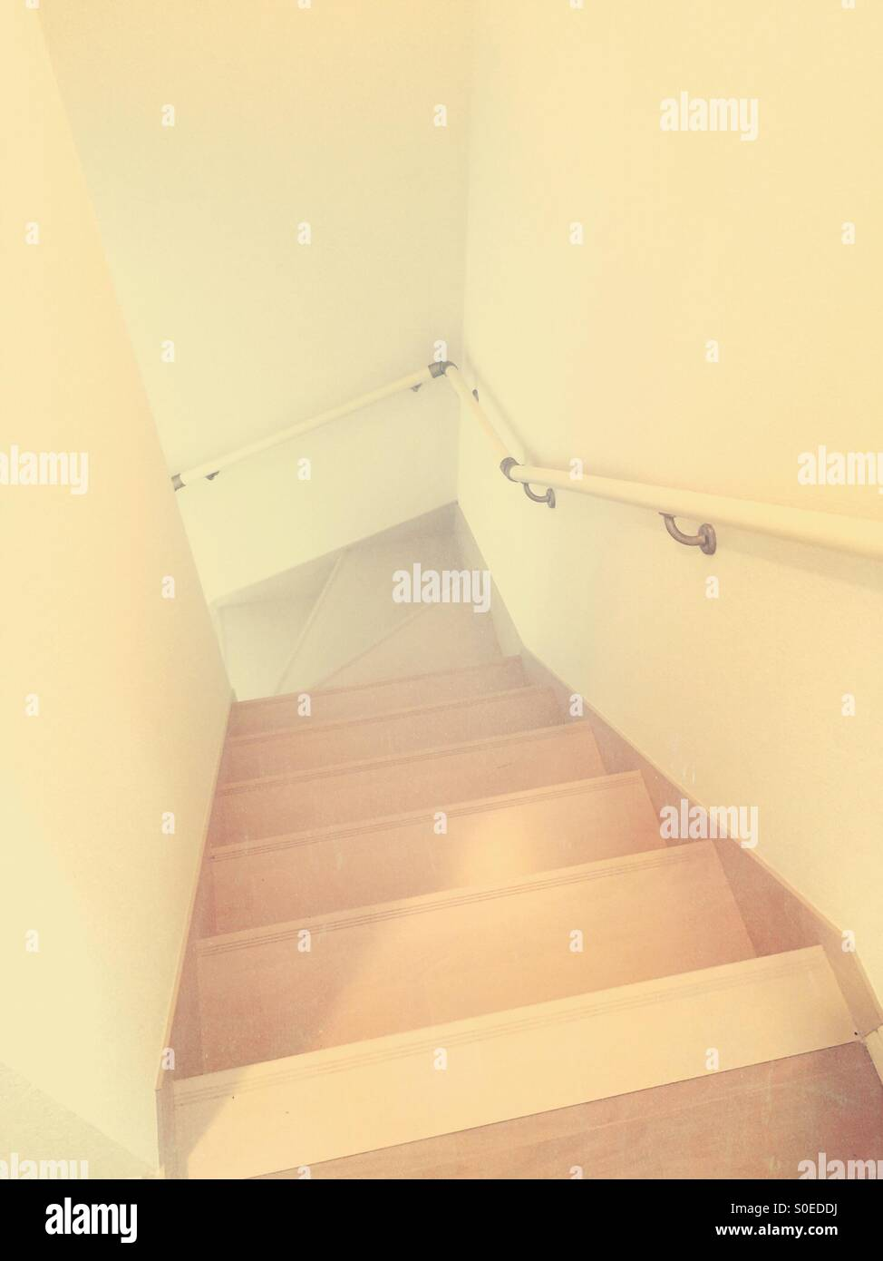 Simple, narrow staircase with light brown wood, white walls and handrail. Vintage paper texture overlay.Stock Photo