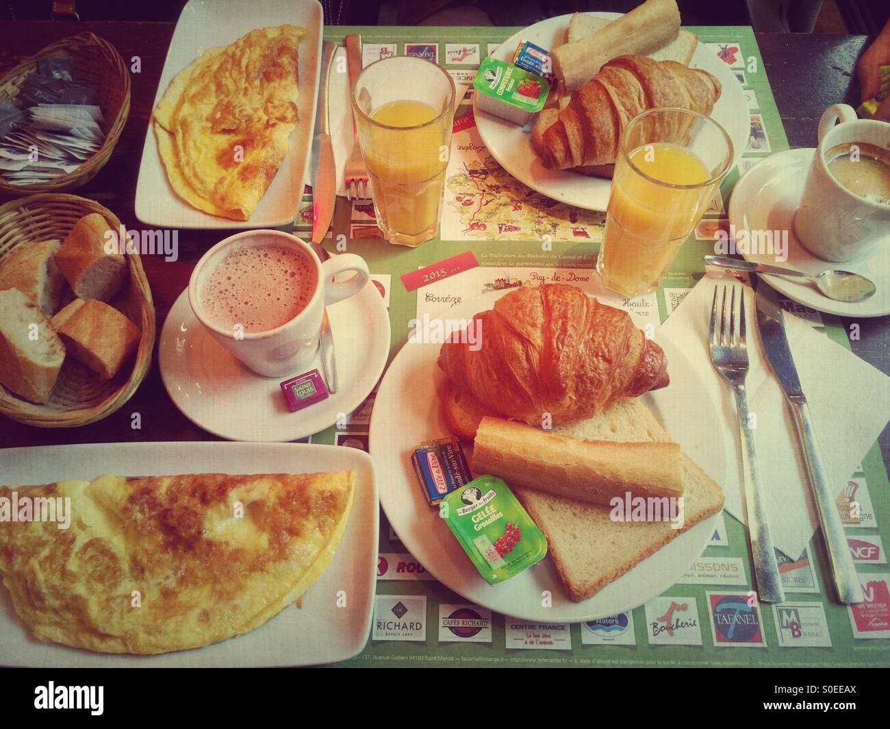 Typical French cafe breakfast at Le Musset brasserie in Paris, France. Croissant, coffee, hot chocolate, orange Stock Photo