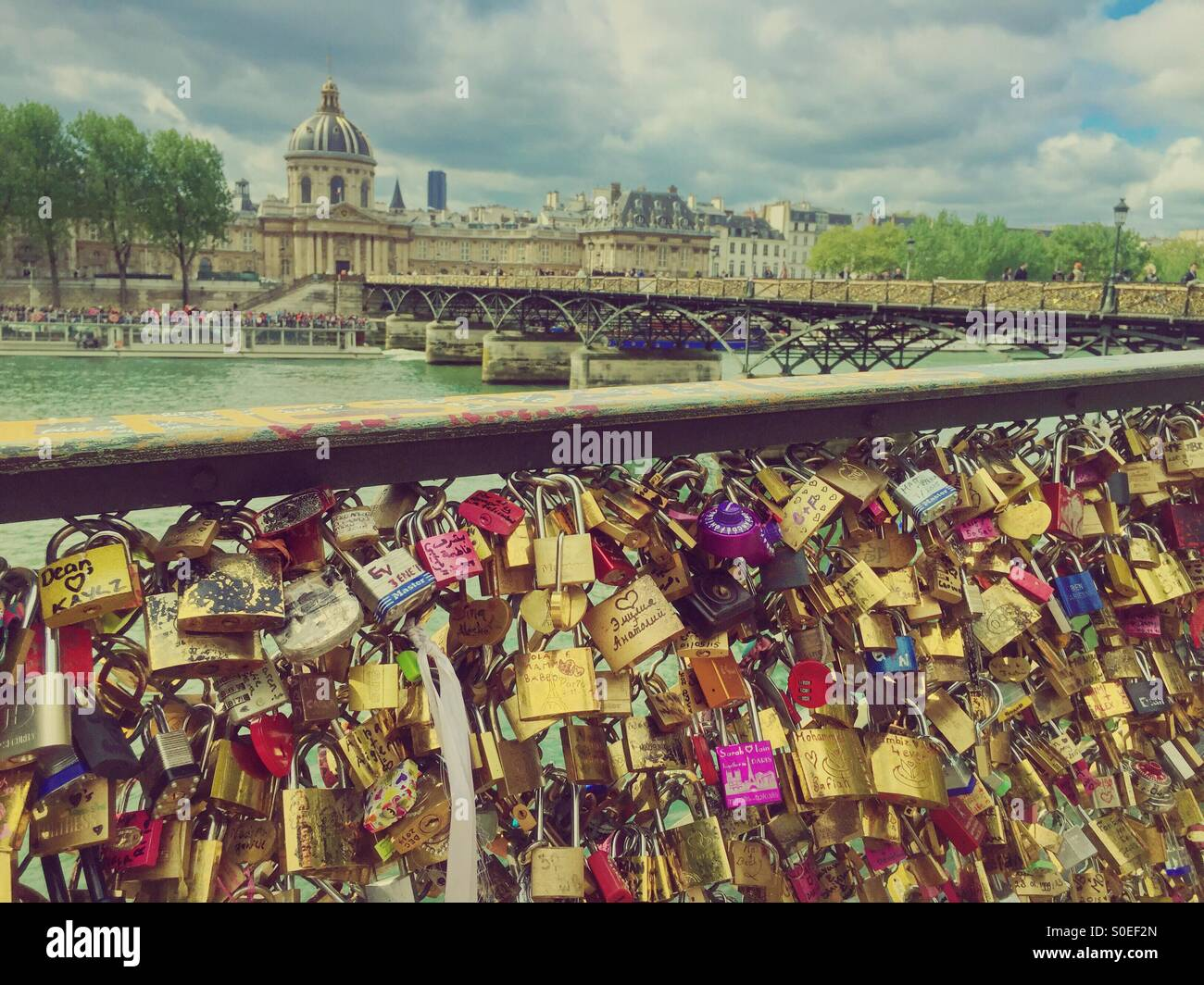 Pont des Arts or Passerelle des Arts, a pedestrian bridge in Paris, France with side panels covered in padlocksStock Photo