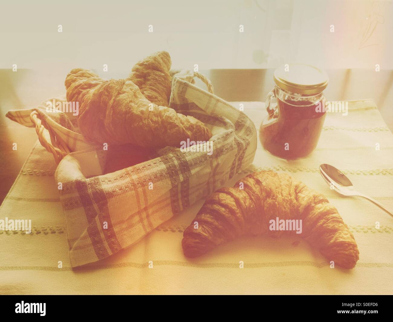 Small jar of homemade strawberry jam, bread basket with croissant, striped cloth and silver spoon. Warm, retro tones. Stock Photo