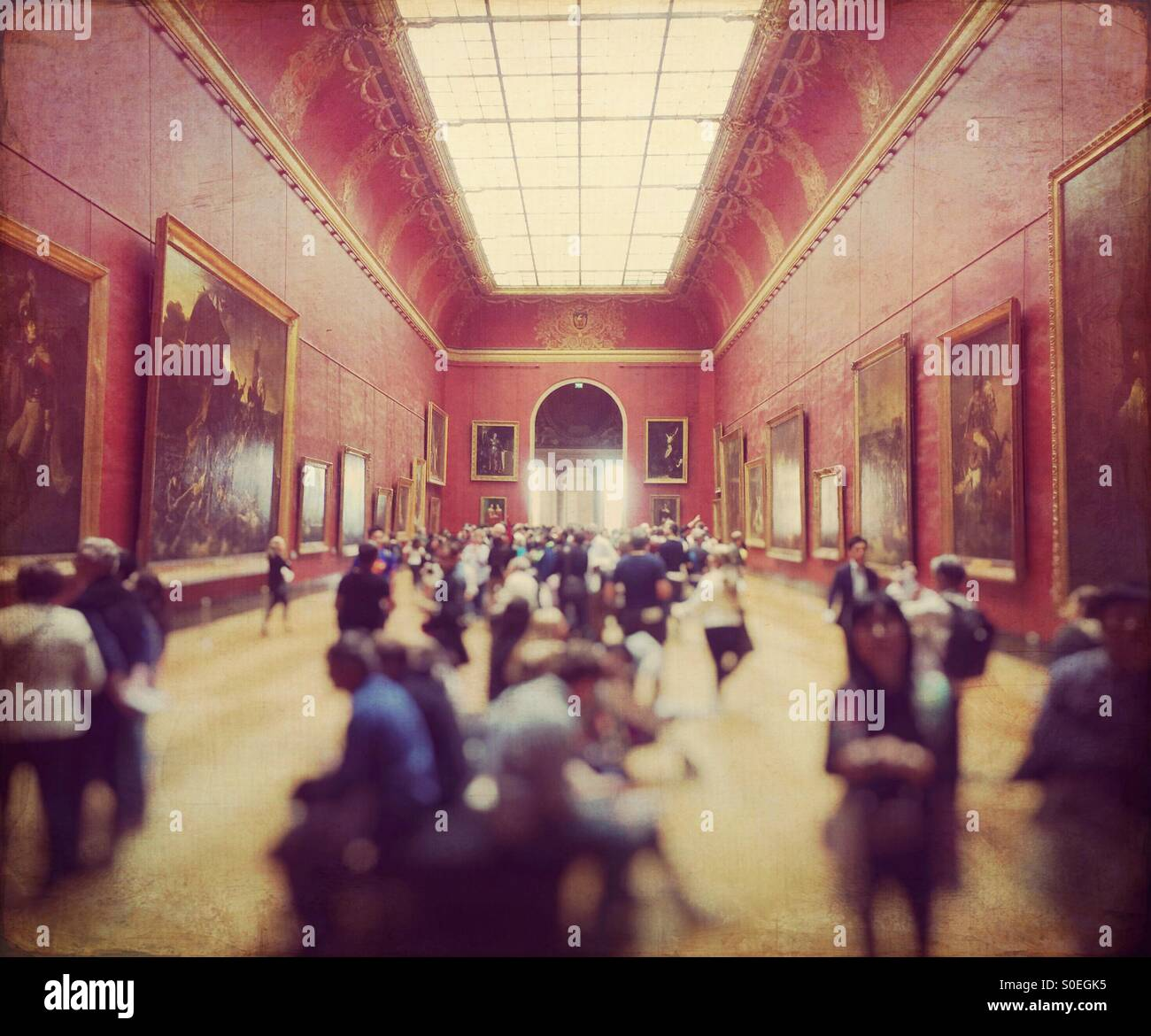 Crowd of tourists in the Red Room gallery at the Louvre museum in Paris, France. Vintage texture overlay.Stock Photo