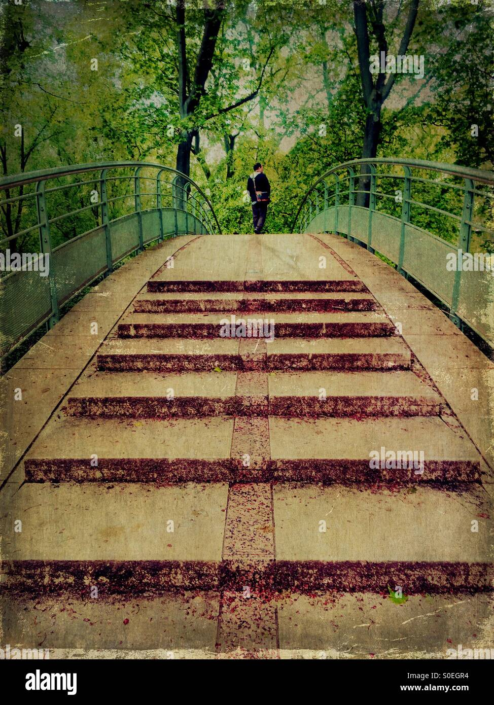 Man crossing an overpass pedestrian bridge at Bercy in Paris, France. Vintage texture overlay. Stock Photo