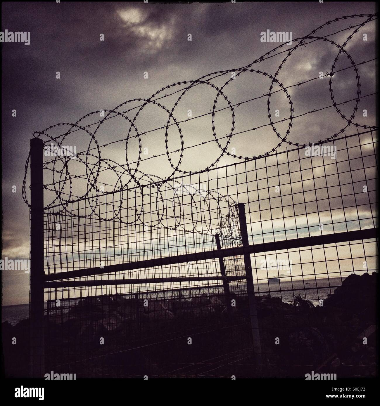 Barbed wire fence at Cape Town harbour. - Stock Image