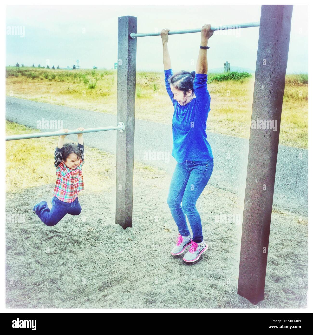 A mother and child each find adjoining pull-up bars just their size for exercise and playtime fun outdoors near - Stock Image