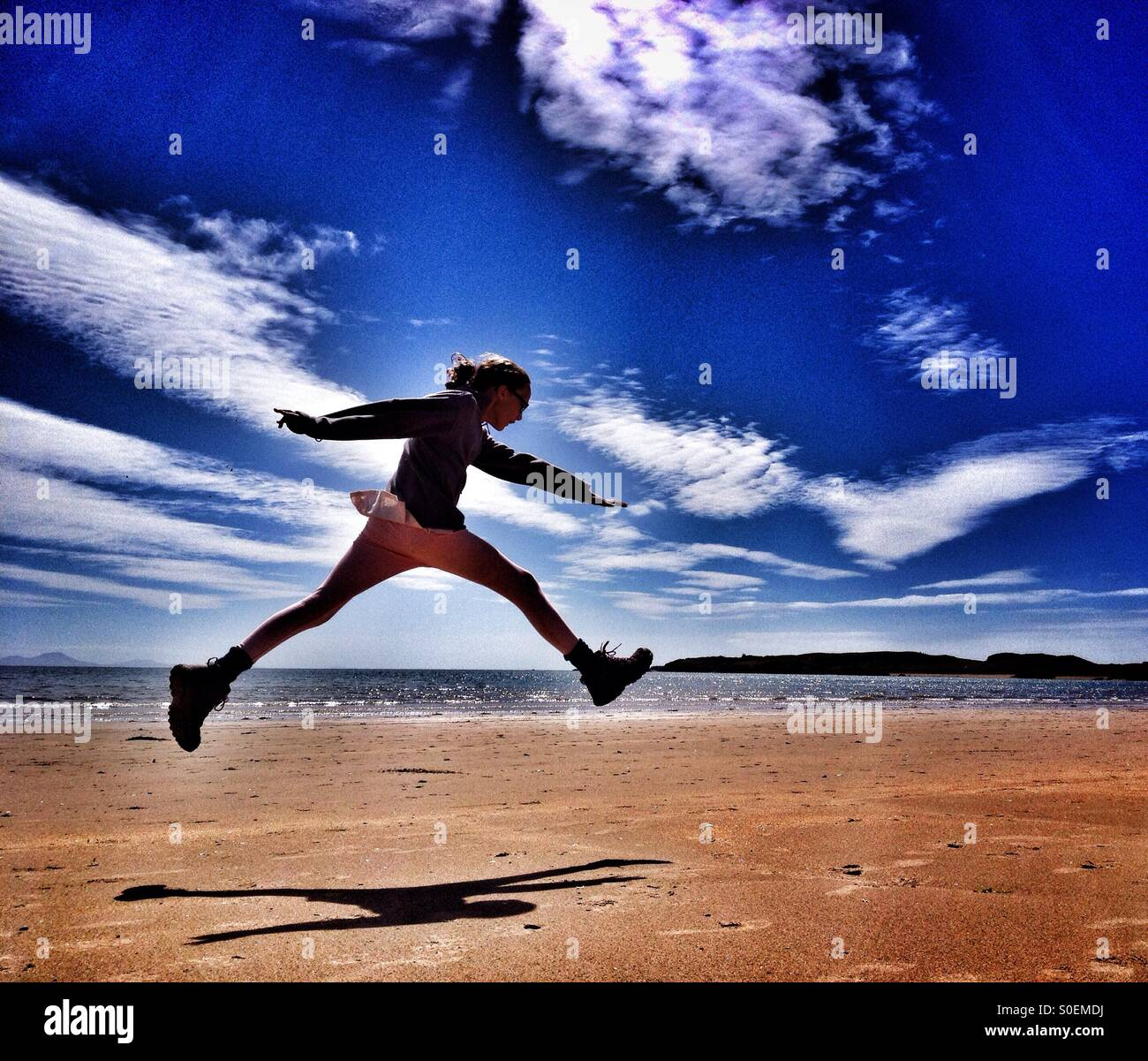 Leap for joy on Newborough beach, Anglesey - Stock Image