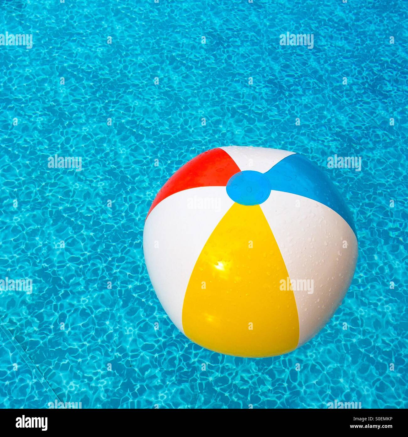 Beach ball in outdoor pool. (Yellow side dominant). - Stock Image