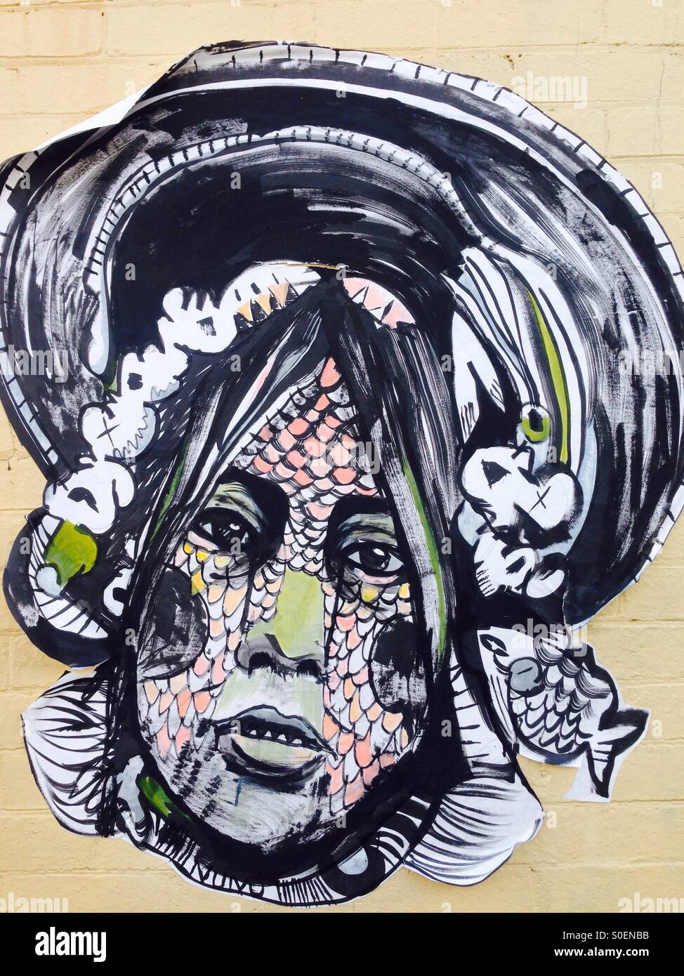 Street art of woman's face with fish scales - Stock Image