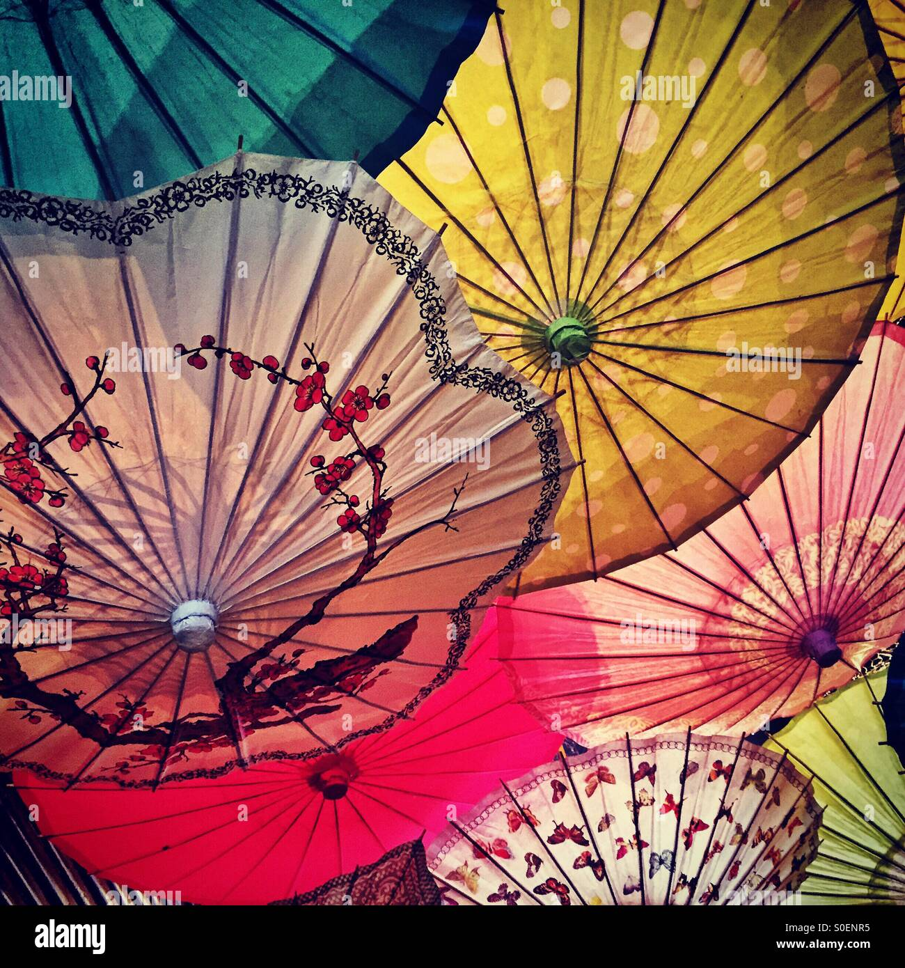 Colorful umbrellas hang from the ceiling over a source of light for a colorful and charming ambiance. - Stock Image