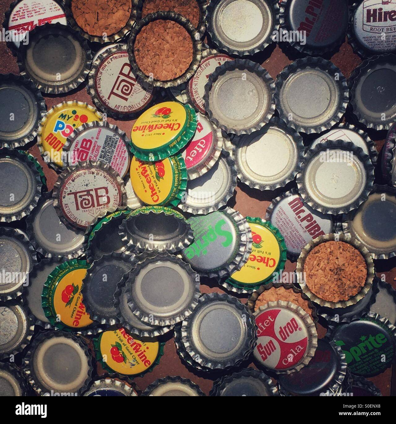 A collection of old vintage bottle caps from various types of sodas. - Stock Image
