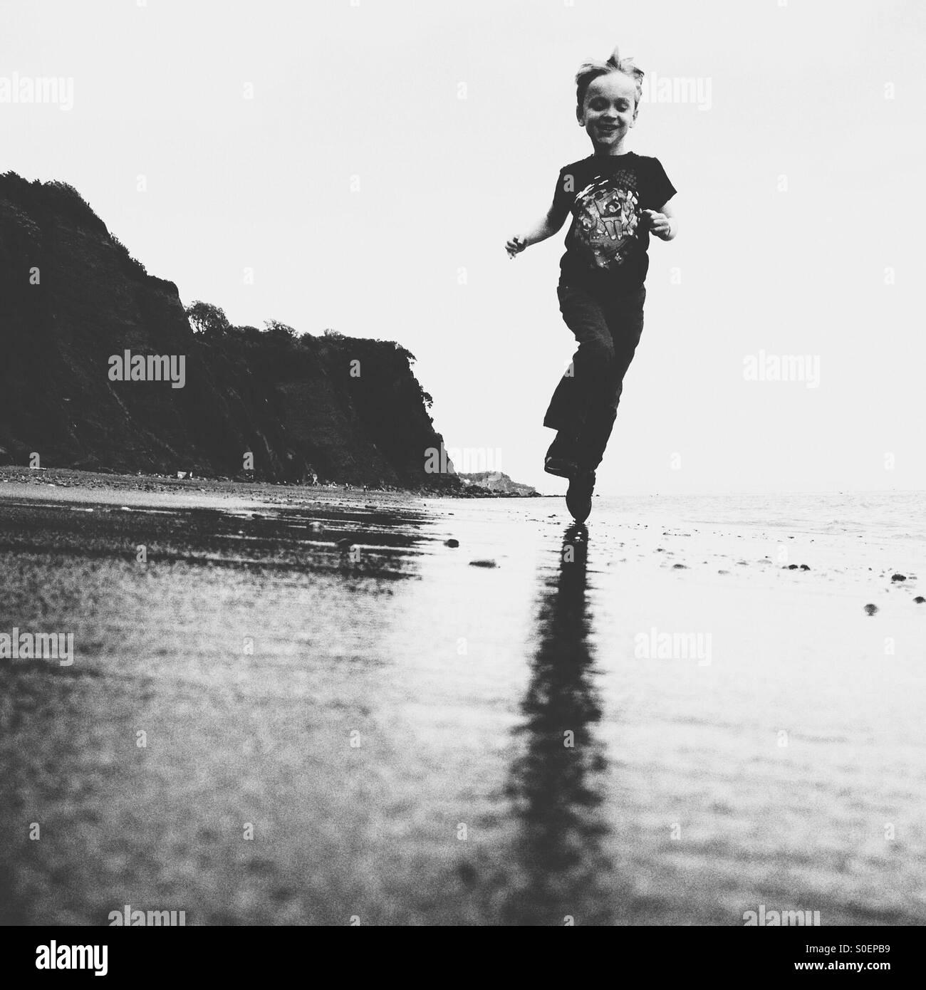 Boy running on a beach - Stock Image