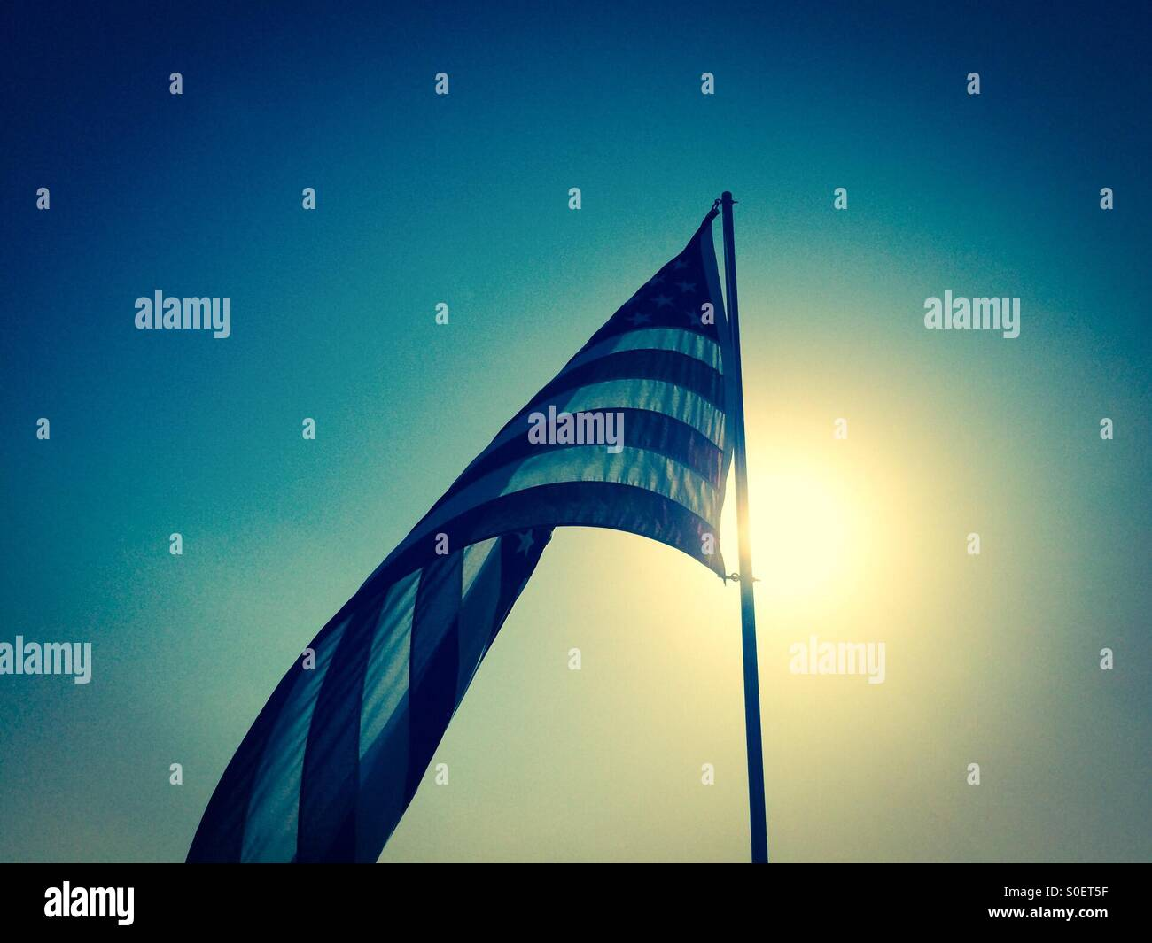 American flag outside on a flagpole with the morning sun behind it - Stock Image