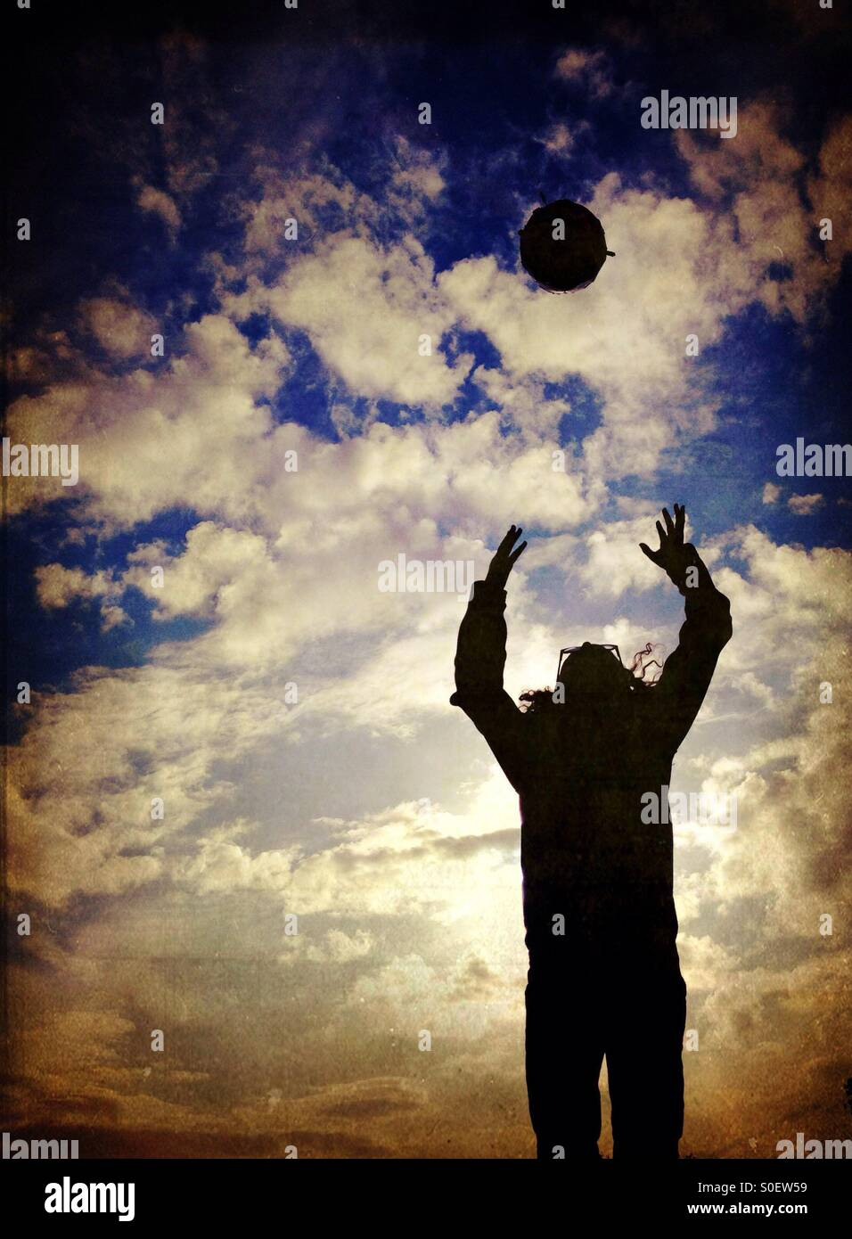 Young girl in silhouette jumping to catch ball - Stock Image