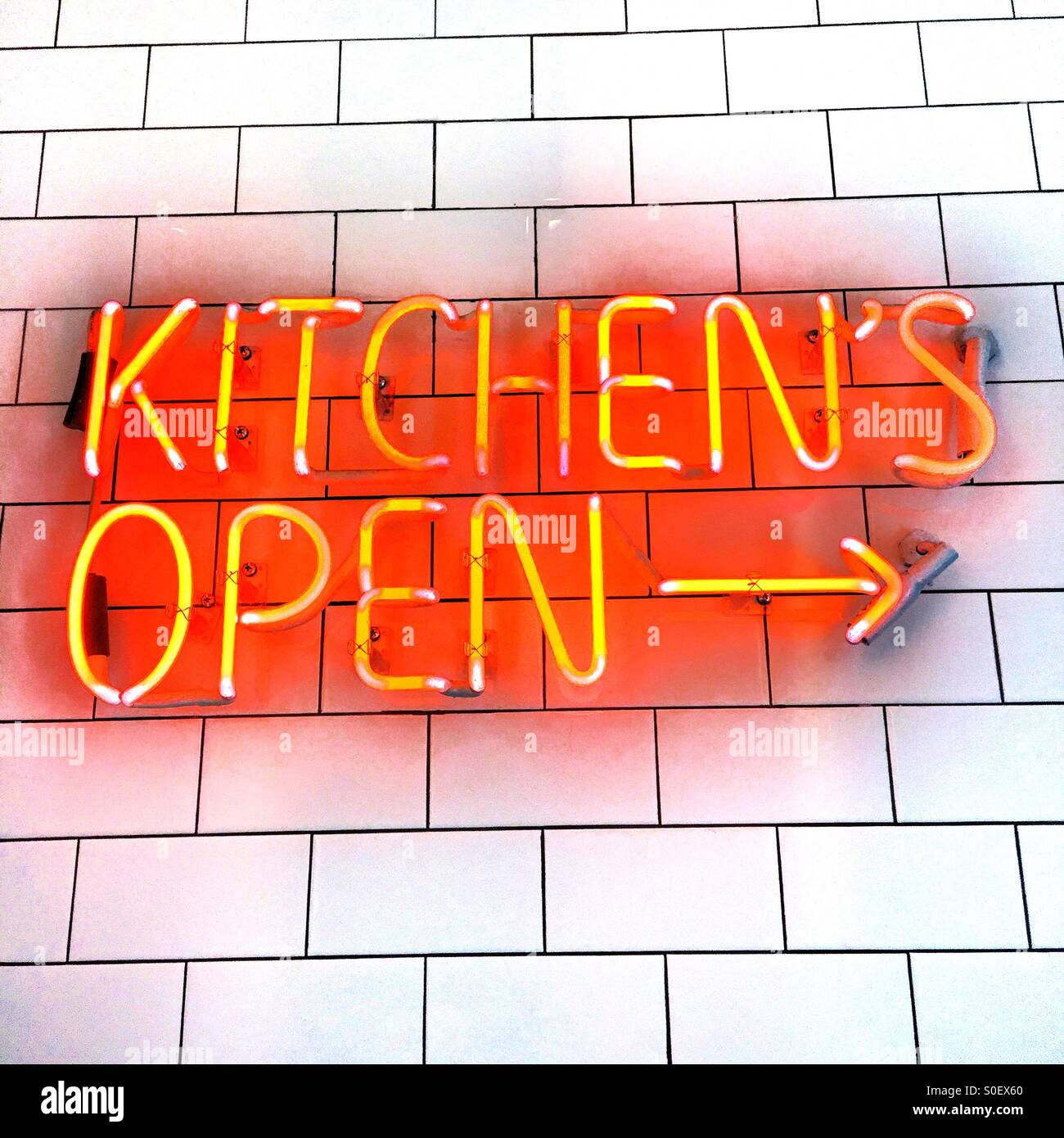 A Bright Red And Yellow Neon Sign On S White Tile Wall