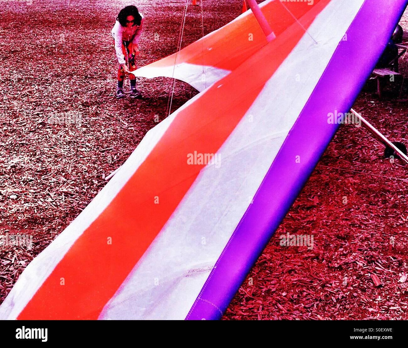 Young woman hang glider preflight rig check in Northern California - Stock Image