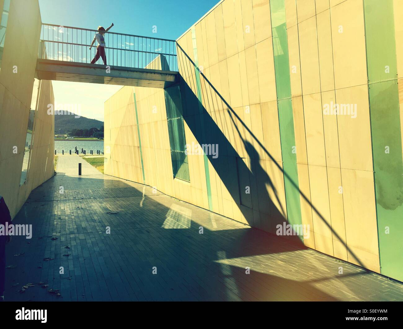 A boy striding across a bridge over an underpass - Stock Image