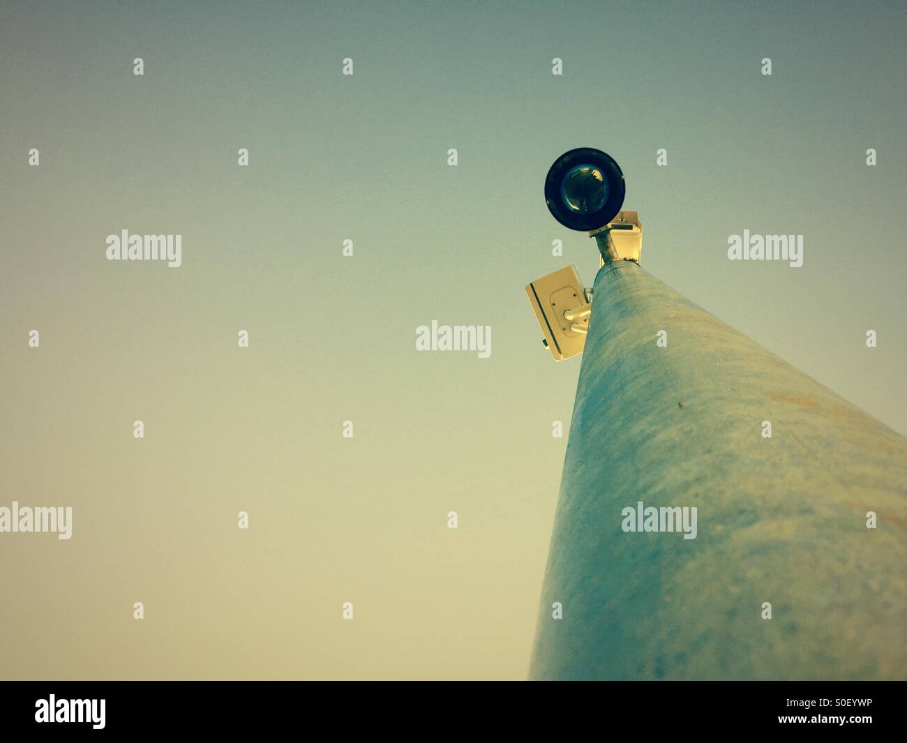 A CCTV camera on a mast watching - Stock Image
