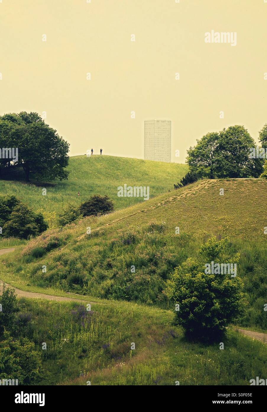 City office block above a green parkland with two silhouetted figures - Stock Image
