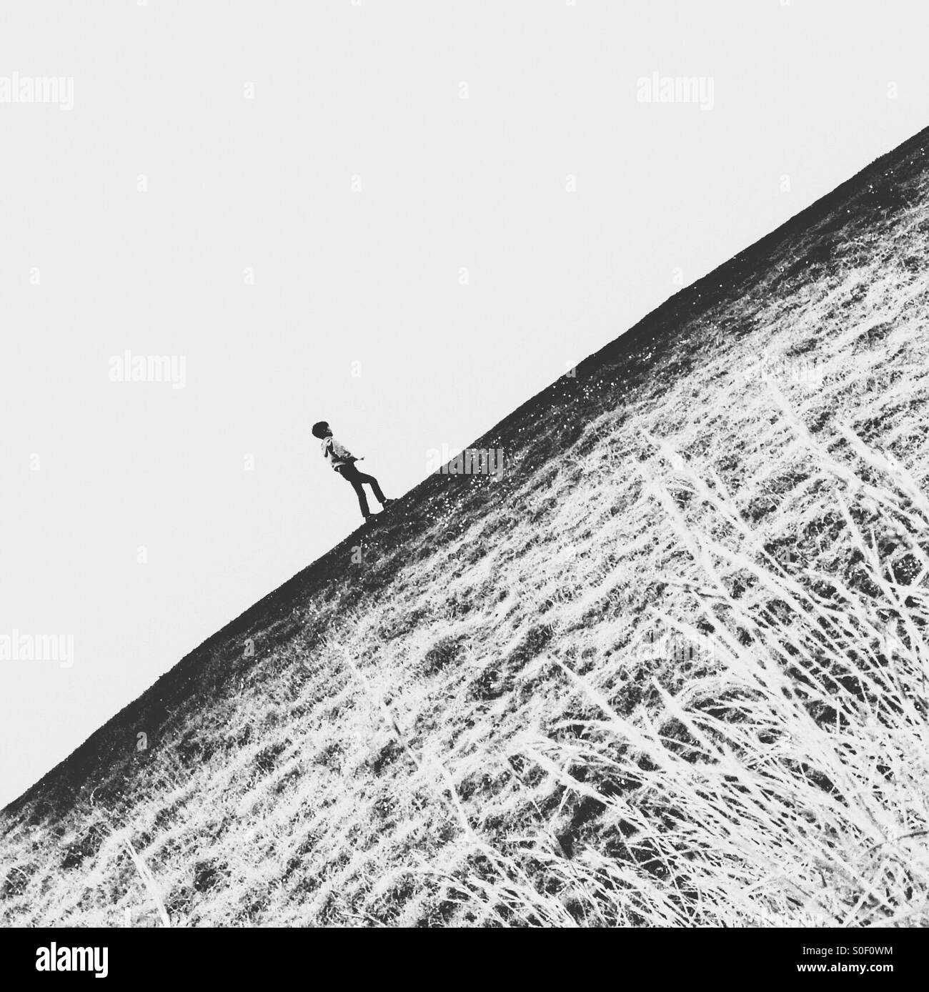 Boy walking up hill - Stock Image