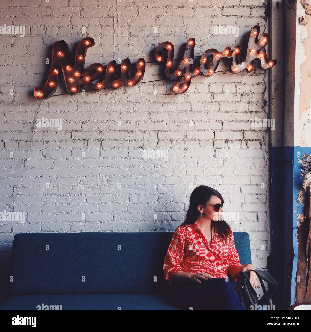 New York Wall Sign and Woman Sitting Stock Photo