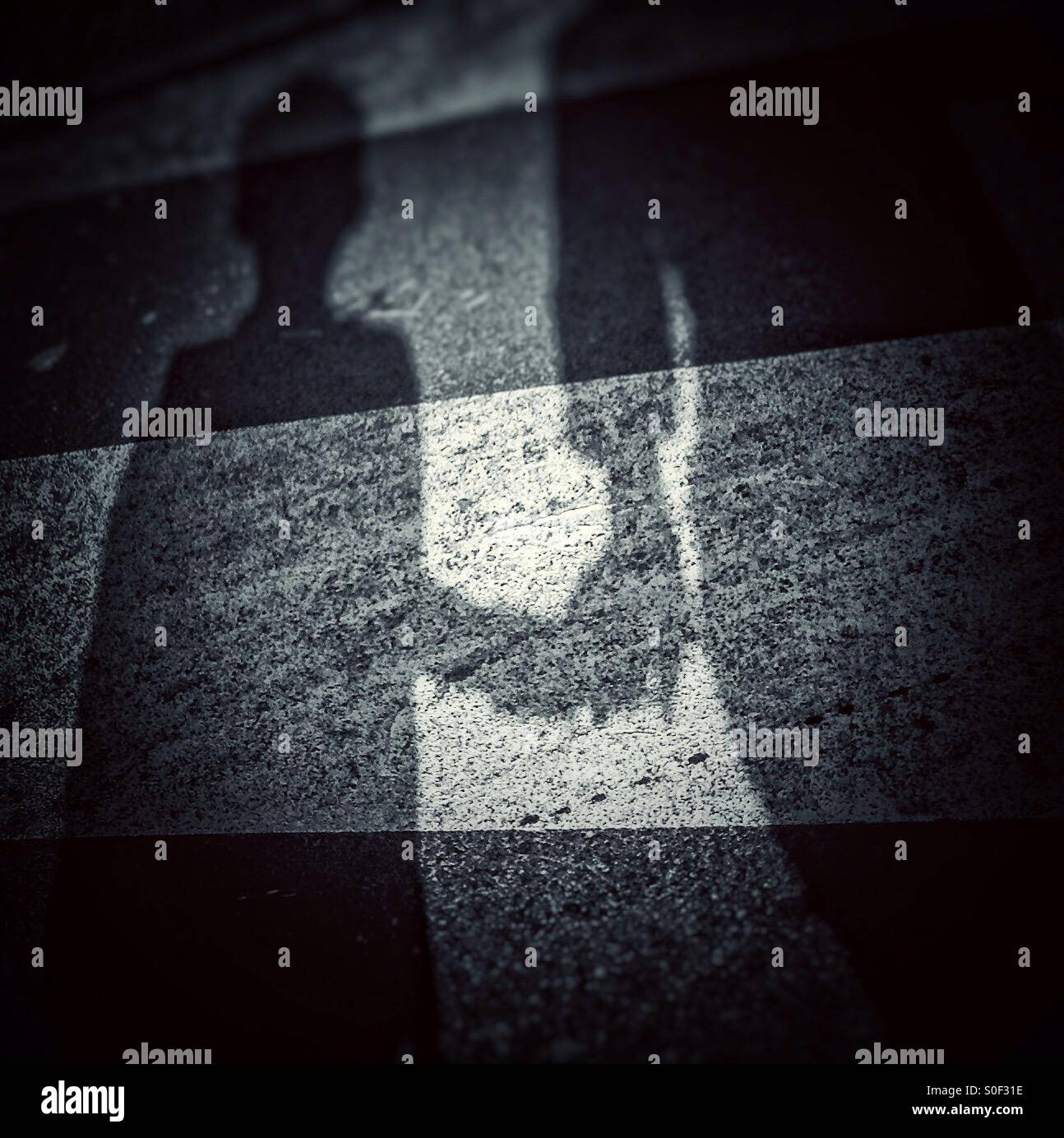 Shadow of an adult holding a hand of a kid over a zebra crossing - Stock Image
