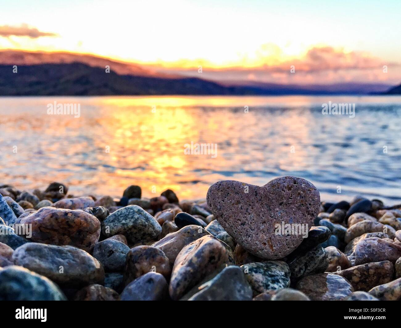 Summer love. Heart shaped rock on the beach with lake and mountains in the background at sunset offer a romantic - Stock Image