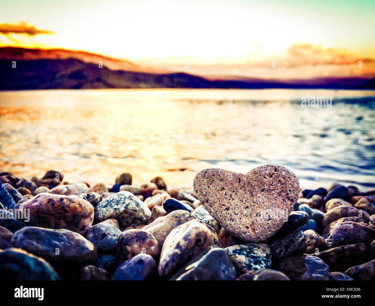 Summer Love. The highlight is on the heart shaped rock sitting on the beach in the foreground. Sunset over lake - Stock Image