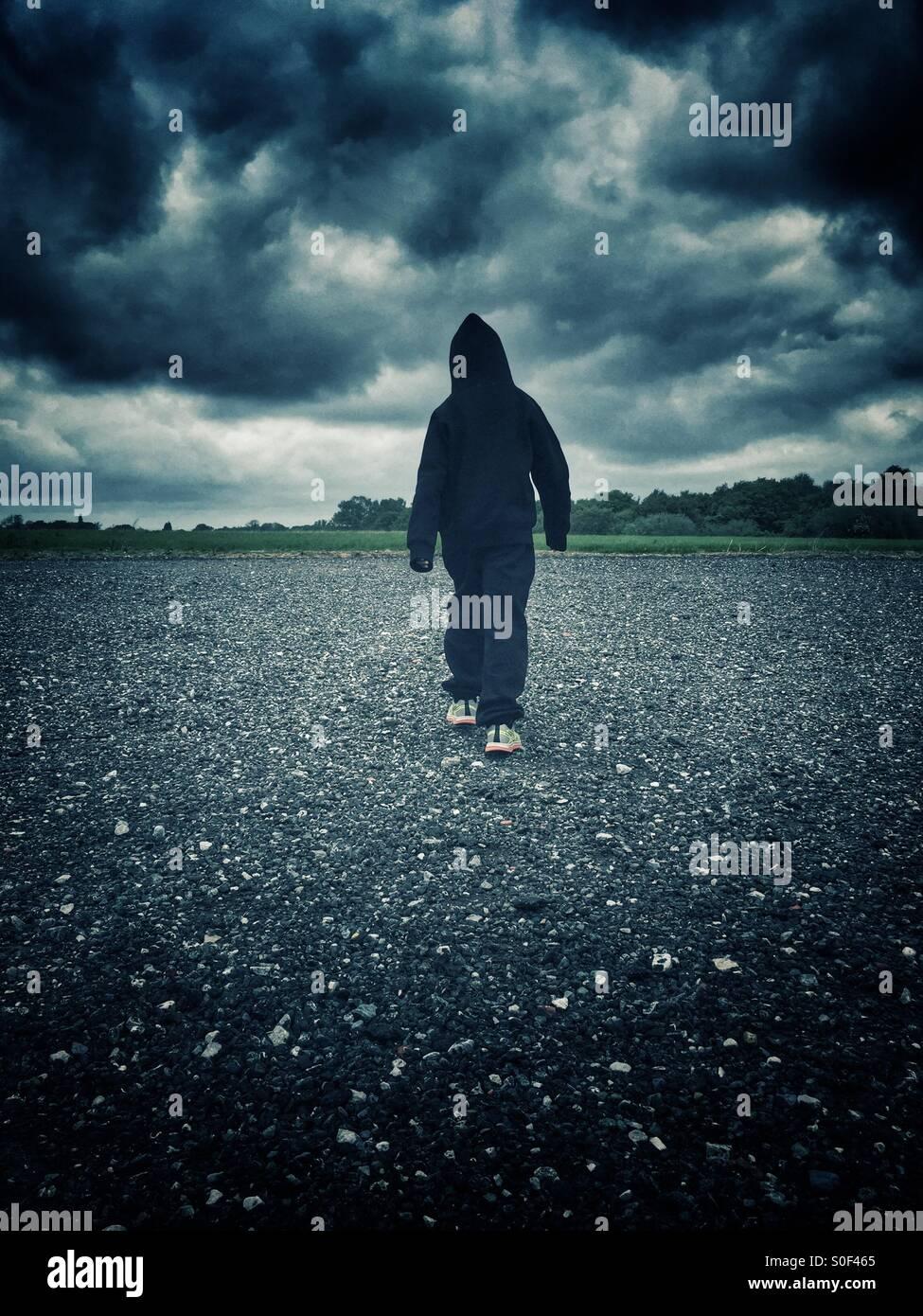 Hooded child walking alone Stock Photo
