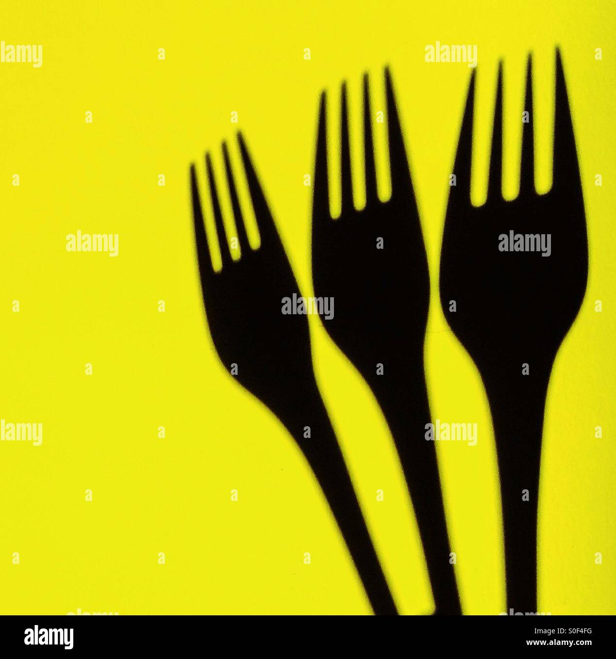 Three forks on yellow background - Stock Image