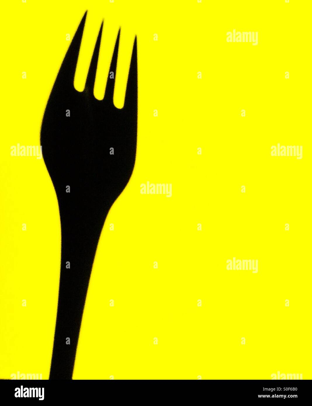 A fork on yellow background - Stock Image