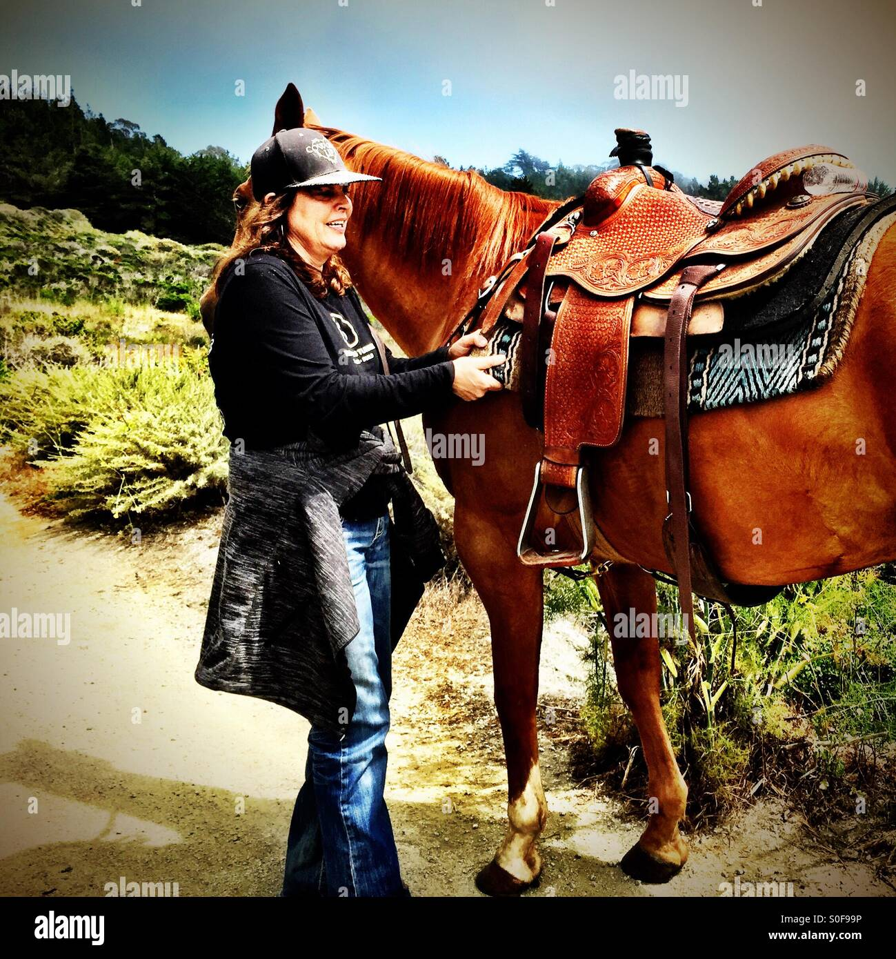 Woman fastening the buckles on her horse's saddle on a fire road, McNee Ranch State Park, California, USA. - Stock Image