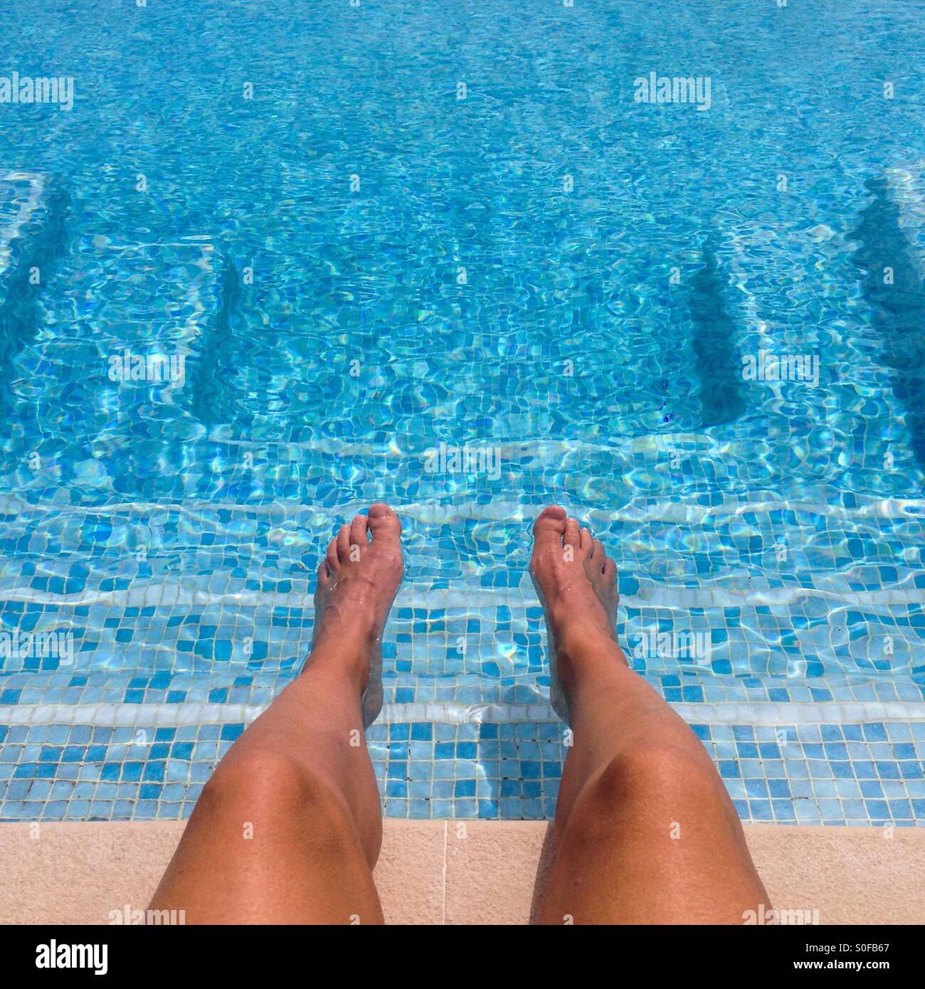 Feet and legs on a swimming pool with a square shape of steps - Stock Image