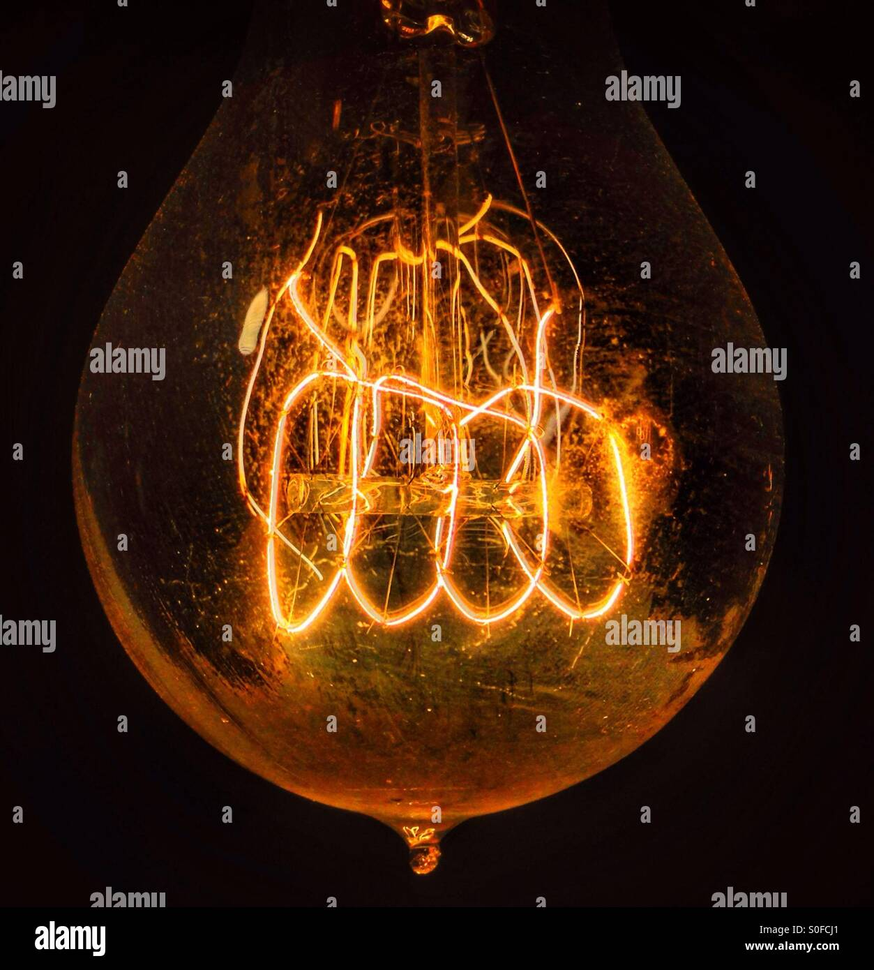 The coil of a burning lightbulb is seen. - Stock Image