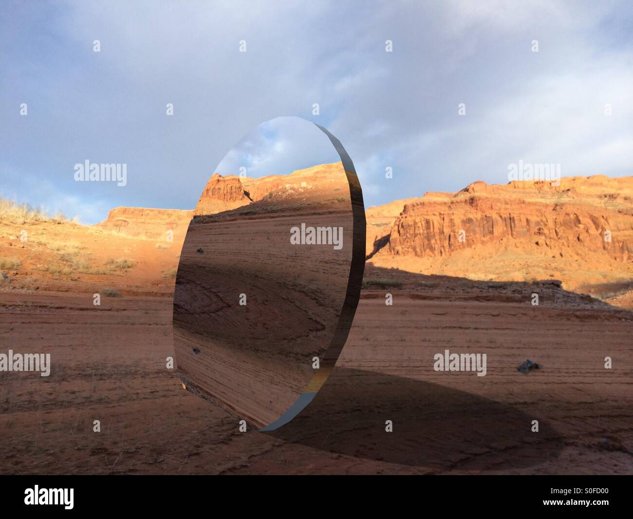 Large round mirror in desert - Stock Image