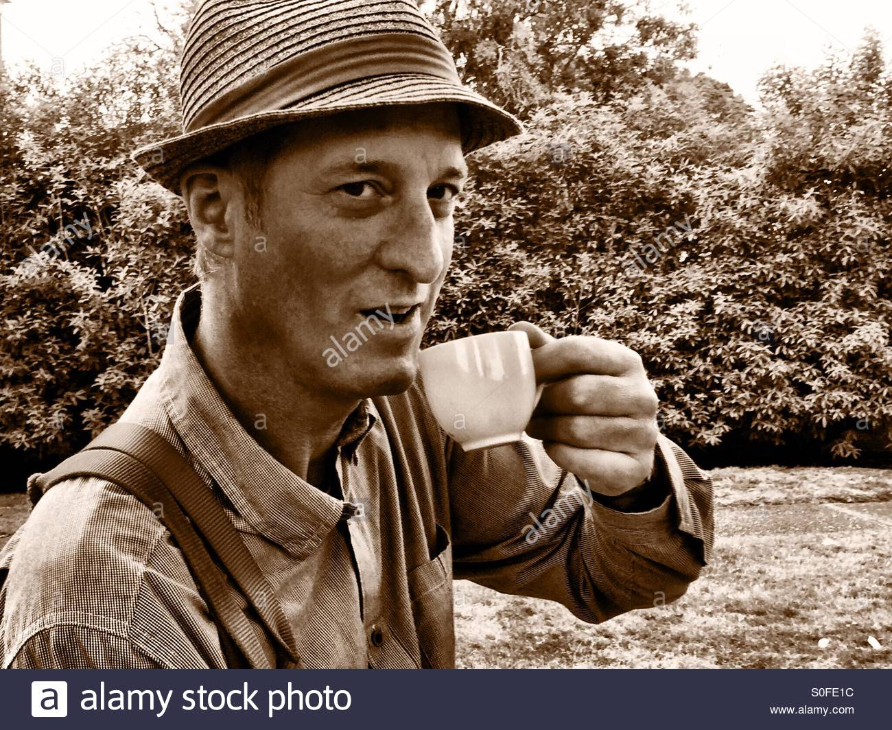 American man having a neighborly weekend chat over a cup of coffee in the backyard. Straw hat, suspenders. Sepia - Stock Image