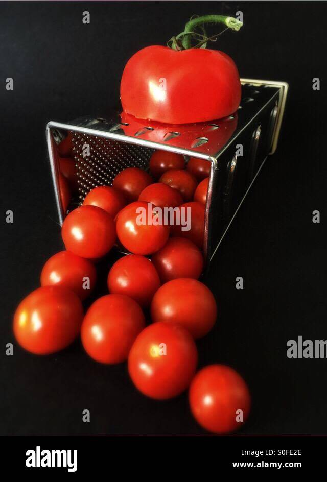 Big tomato is grated to produce small tomatoes - Stock Image